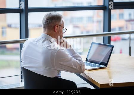 Male freelancer is working in a cafe on a new business project. Sits at a large window at the table. Looks at a laptop screen with a cup of coffee