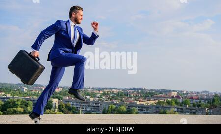 Entrepreneur in motion purposeful expression. Businessman formal suit carries briefcase sky background. Businessman hurrying to business meeting. I will be there in minute. Keep going towards goal.