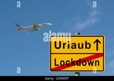 symbolic picture, end of lockdown, start vacation, travelling, composing, yellow German city limit sign, passenger plane taking off, Germany