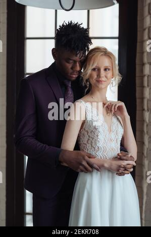 Interracial couple standing in front of a big window. Interracial bridal photoshoot. Caucasian woman getting married with african dark skinned