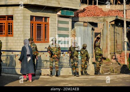 A woman walks past Indian army soldiers standing alert near the site of an attack in Srinagar, the summer capital of Jammu and Kashmir. Two Indian army soldiers were killed in a militant attack on the outskirts of Srinagar. The soldiers were part of an Army patrol team that came under heavy firing from militants, police said. (Photo by Saqib Majeed / SOPA Images/Sipa USA)  Stock Photo