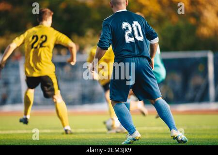 Adult Men Playing European Football Soccer. Footballers Running and Kicking Game. Adult Football Players Compete in Soccer Match. Soccer Bench and Sub - Stock Photo