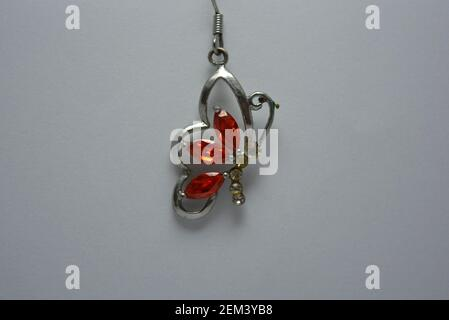 Women's jewelry, earrings in the form of a metal butterfly with red, orange stones, located on a white background.