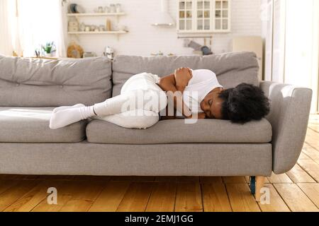 Depressed unhappy African woman lying on couch at home, crying, suffering from divorce or break up.