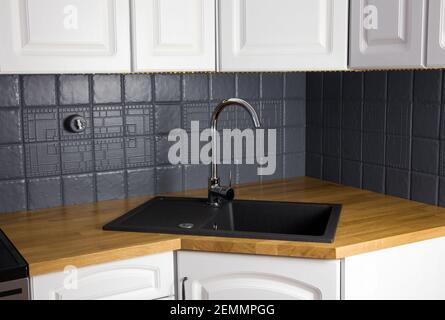 Close up view of new modern kitchen solid wood oak counter with built in black rectangular granite sink, repainted gray color tile wall. Corner.