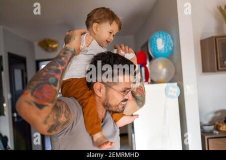Happy father carrying son on shoulder while standing at home