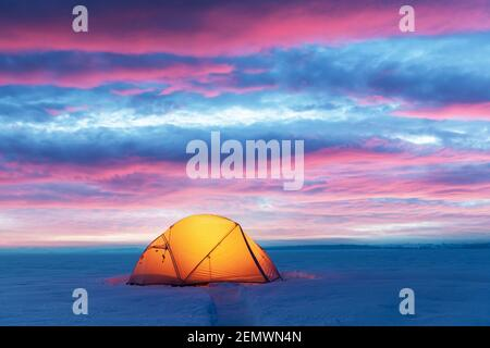 Yellow tent lighted from the inside by a flashlight against the backdrop of glowind pink sky. Amazing snowy landscape. Tourists camp in winter field. Travel concept