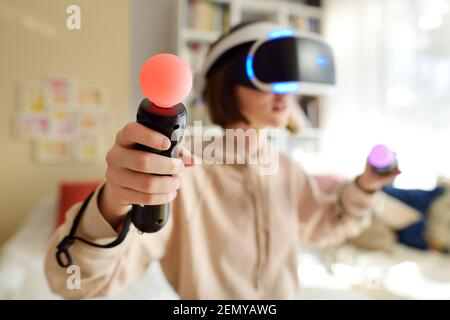 Pretty teenage girl wearing virtual reality headset at home. Cute teen using VR glasses to play a game. Child in virtual augmented reality helmet. Fut