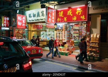 Hong Kong, China. Night shopping scene in Wing Lok Street, Sheung Wan. Traditional shops. - Stock Photo