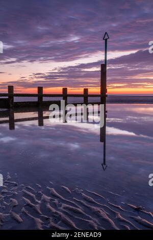 Sunset over Rhyl beach at low tide on the North Wales coast - Stock Photo