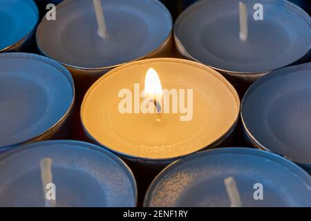 Closeup of tea lights with one being lit. A single warm orange flame between  candles in blue shadow. Christmas, condolences or funeral background.