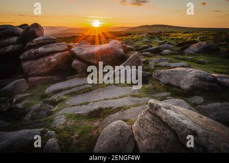 Sunset on Higger Tor in Peak District, UK.Sun setting over hills and moorland with rocks.Tranquil evening landscape scenery