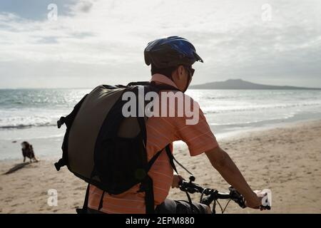 A cyclist riding along Milford beach with Rangitoto Island in the background and a dog playing on the beach