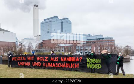 28 February 2021, Hamburg: Activists of the environmental protection organization Robin Wood demonstrate in front of the Tiefstack power plant behind a banner reading 'Heating with wood from Namibia? Unfair and harmful to the climate! The Hamburg environmental authority is currently examining the possibility of burning wood from Namibia instead of coal at the Tiefstack power plant. The project is one of the first internationally for which wood from Africa is to be supplied on a large scale to an EU country for energy production. Photo: Markus Scholz/dpa - Stock Photo