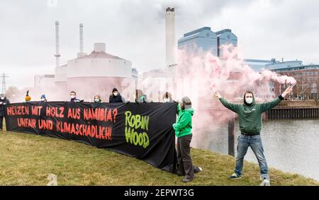 28 February 2021, Hamburg: Activists of the environmental protection organization Robin Wood demonstrate in front of the Tiefstack power plant behind a banner reading 'Heating with wood from Namibia? Unfair and harmful to the climate! Hamburg's environmental authority is currently examining the possibility of burning wood from Namibia instead of coal at the Tiefstack power plant. The project is one of the first internationally for which wood from Africa is to be supplied on a large scale to an EU country for energy production. Photo: Markus Scholz/dpa - Stock Photo