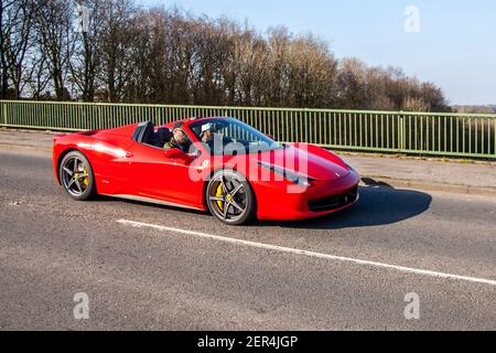 2014 red Ferrari 458 Spider Dct S-A sports car; Vehicular traffic, moving vehicles, cars, vehicle driving on UK roads, motors, motoring on the M6 motorway highway UK road network