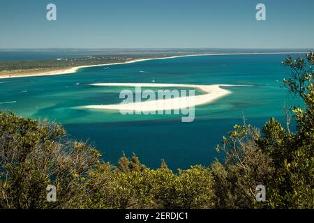Sand bank in front of Tróia beach in Portugal, surrounded by turquoise waters with moored pleasure boats and in the background the beach line.