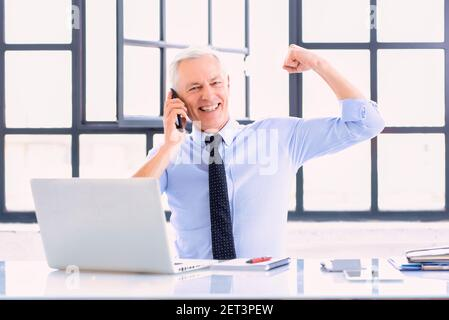 Shot of successful businessman talking with somebody on mobile phone and celebrating in his workplace while sitting in front of laptop.