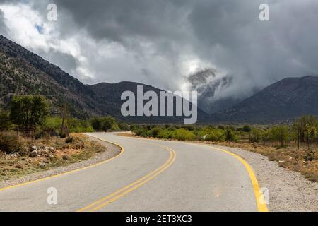 Dramatic clouds over a road and mountainous landscape near the Samaria Gorge trailhead, Crete, Greece