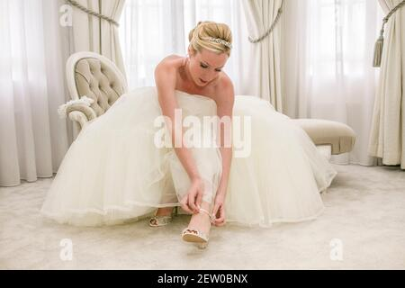 Bride sitting down on chaise lounge within bridal suit bucking her shoe strap