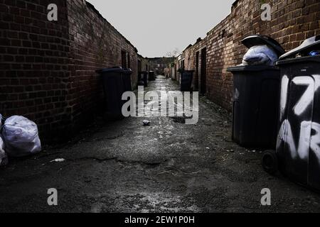 A back street or alleyway between run down terraced houses in the North of England UK with dustbins and wheelie bins waiting for collection Stock Photo
