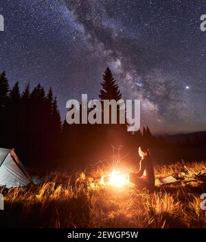 Side view of female tourist having a rest by campfire on background of tent and spruce forest under starry sky on which milky way is visible. Bonfire with a big flame under the night sky