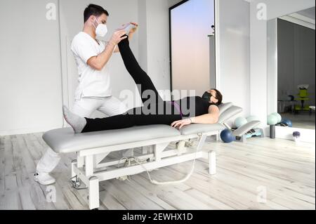physiotherapist doing leg muscle stretching to female patient. Treatment of a woman's sciatic nerve. High quality photo. Stock Photo