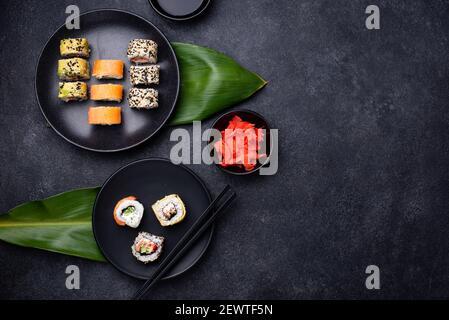 Traditional Japanese sushi rolls on dark background