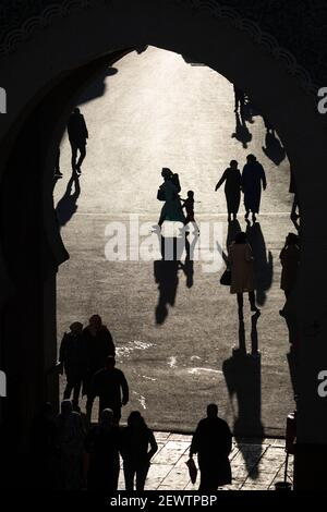 View through the Blue Gate (Bab Bou Jeloud) of pedestrians casting long shadows on the ground, Fes, Morocco - Stock Photo