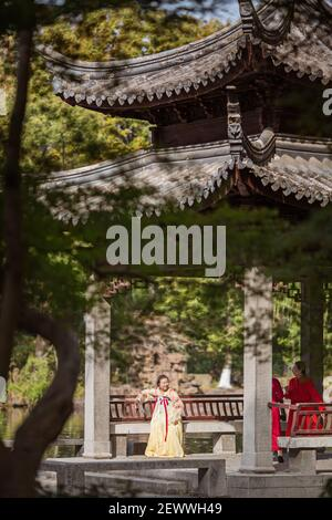 Huzhou, China, 18 November 2020: Chinese woman wearing traditional dress and holding fan in park in China. Happy Spring Festival, Chinese New Year