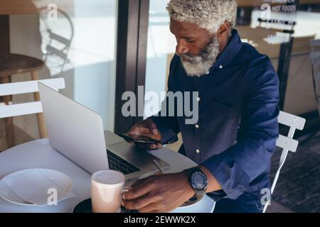 African american senior man sitting at table outside cafe using laptop and smartphone - Stock Photo