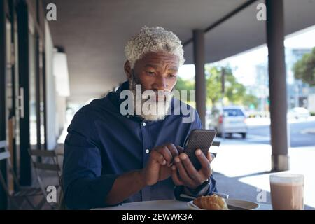African american senior man sitting at table outside cafe with coffee using smartphone - Stock Photo