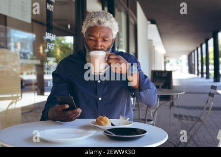 African american senior man sitting at table outside cafe drinking coffee and using smartphone - Stock Photo