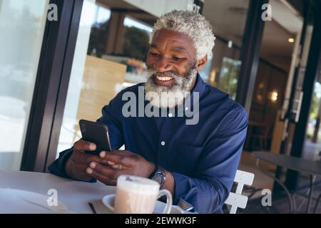 African american senior man sitting at table outside cafe with coffee using smartphone and smiling - Stock Photo