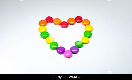 Selective focus of colorful button chocolates arranged in the shape of a heart on a white paper background. - Stock Photo