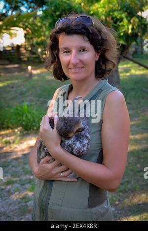 Woman holding a young Pale-throated three-toed sloth (Bradypus tridactylus), French Guyana