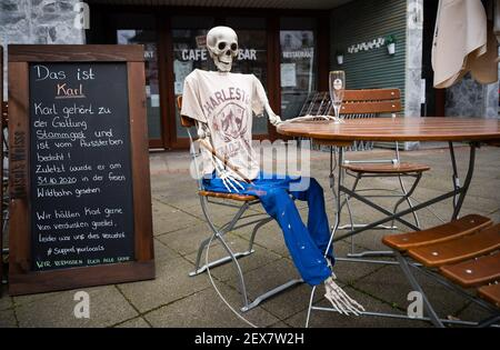 04 March 2021, Lower Saxony, Hanover: A skeleton sits with an empty beer glass outside a restaurant closed due to the Corona pandemic in Südstadt. The lockdown in Germany is extended until March 28. Photo: Julian Stratenschulte/dpa