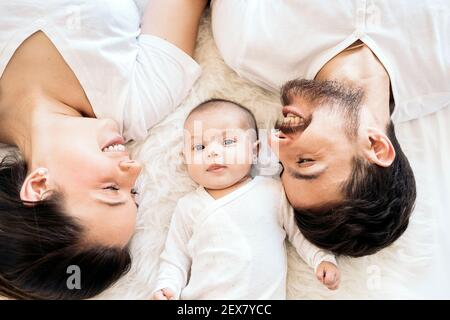 Stock photo of happy and young parents lying in bed with their young baby.