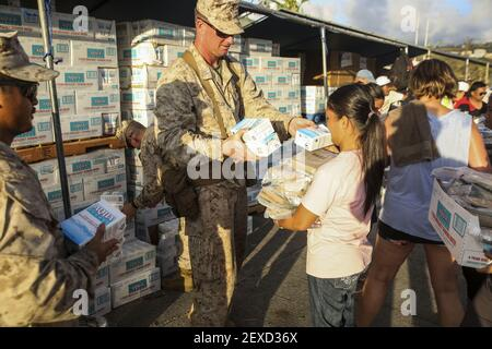 SAIPAN (Aug. 9, 2015) U.S. Marine Capt. Jeffery Butler distributes water at a shelter in Saipan, Aug. 9, 2015. Marines assigned to Echo Company, Battalion Landing Team 2nd Battalion, 5th Marines, 31st Marine Expeditionary Unit (31st MEU), are assisting local and federal agencies with typhoon relief efforts in Saipan after the island was struck by Typhoon Soudelor, Aug. 2-3. (Photo Cpl. Ryan C. Mains/U.S. Marine Corps) *** Please Use Credit from Credit Field ***
