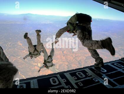 Marines with Force Reconnaissance Company and Reconnaissance Training Company, 1st Reconnaissance Battalion, 1st Marine Division, jump from a C-130J Super Hercules aircraft during High Altitude – High Opening parachute insertion training over Marine Corps Base Camp Pendleton, Calif., Sept. 17, 2015. The goal of the training was to sharpen a skill set that is of great advantage to expeditionary forces, allowing the jumpers to infiltrate locations where access would be too difficult for vehicles. (Photo by Pfc. Devan Gowans/U.S. Marine Corps) *** Please Use Credit from Credit Field *** Stock Photo