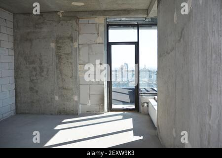 An inside view of an empty newly constructed apartment, flat without repair with a window installed in a newly built, erected residential building.