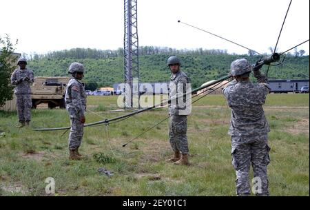 U.S. Soldiers with the 187th Signal Company, New York Army National Guard, raise an OE254 antenna during scenario-based exercise eXportable Combat Training Capability at Camp Grayling Joint Maneuver Training Center, Mich., July 14, 2014. (Photo by Pfc. Gabrielle Scibetta, U.S. Army National Guard/DoD/Sipa USA)