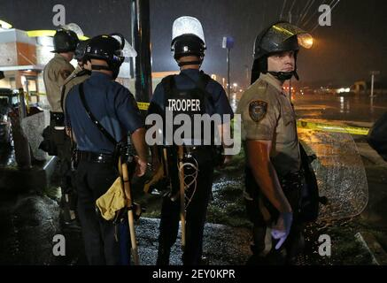 Missouri Highway Patrol officers and St. Louis County police stand at the ready in the rain next to the McDonald's on West Florissant Avenue in Ferguson, Mo., on Saturday, Aug. 16, 2014, several minutes after the curfew started at midnight. Most people on the south end of West Florissant in the containment area complied with the curfew. (Photo by J.B. Forbes/St. Louis Post-Dispatch/MCT/Sipa USA)