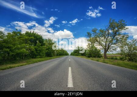 Car-free, empty asphalt country road, highway, on a sunny summer, spring day, receding into the distance, against a blue sky with white clouds and tre