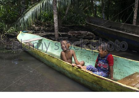 Kids play in one of the local boats used by the Ngobe Indians as their main form of transport, sheltered under a makeshift lean-to. Channel to entrance at The Ngobe Bugle Indian Village Of Salt Creek Near Bocas Del Toro Panama. Salt Creek (in Spanish: Quebrada Sal) is a Ngöbe Buglé village located on the southeastern end of Bastimentos island, in the Bocas del Toro Archipelago, Province and District of Panama. The community consists of about 60 houses, an elementary school, handcrafts and general stores. The villagers depend mostly on their canoes for fishing and transportation although the  Stock Photo