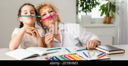 Woman tutor or foster parent mum helping cute caucasian school child girl doing homework sitting at table. Diverse nanny and kid learning writing in