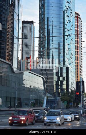 Cars stopped on red light in city intersection with tall buildings with glass exterior walls in background. - Stock Photo