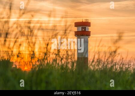 Germany, Lower Saxony, Krautsand: Evening mood. The red-white lighthouse and sunset on the Krautsand Elbinsel.