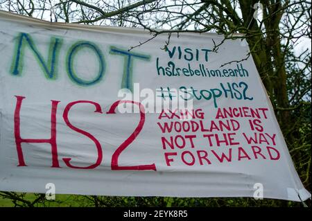Great Missenden, Buckinghamshire, UK. 4th March, 2021. An Anti HS2 banner in the trees. HS2 Ltd have marked 14 majestic oak trees ready for felling along Leather Lane in Great Missenden. Local residents have started a petition to Save Leather Lane Oaks. A new Stop HS2 protest camp has been set to protect the majestic oaks  from imminent destruction by HS2. The controversial High Speed 2 rail link from London to Birmingham is carving a huge scar across the Chilterns which is an area of Outstanding Natural Beauty causing much upset to locals and tree lovers. Credit: Maureen McLean/Alamy