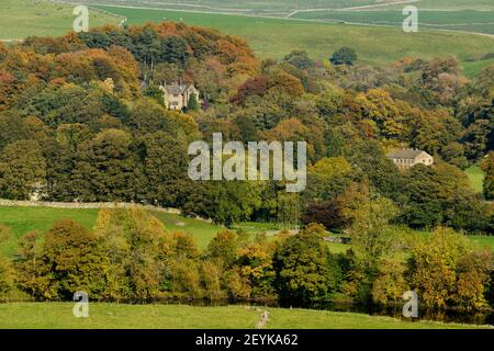 Scenic Wharfedale autumn (River Wharfe, houses nestling in hillside woodland, colourful foliage on trees, upland fields - Yorkshire Dales, England, UK